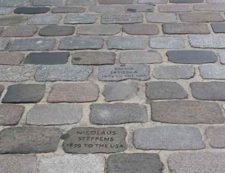 Inschriften neueren Datums findet man auf dem Pflaster vor dem Deutschen Auswandererhaus in Bremerhaven. Sie erinnern an die Menschen, die im 19. Jahrhundert ihr Heimatland verließen.