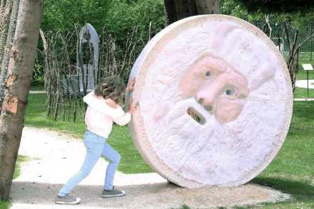 """Helmut Moser: """"Das Grab Jesu"""" (33 n.Chr.) am Eingang zum Parcours. Der Felsenbrocken, der ehemals vor die Gruft gerollt war, ist hier eine Bocca della Verità aus der Antike. Im Mittelalter kam die Sage auf, der jeder, der lügt und seine Hand in ihren Mund liegt, die Hand verliert."""