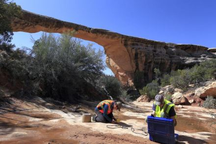 Paul Geimer and Jeff Moore of the University of Utah install a reference seismometer near Owachomo Natural Bridge (background) in Utah. Photo by Jacob Kirkegaard