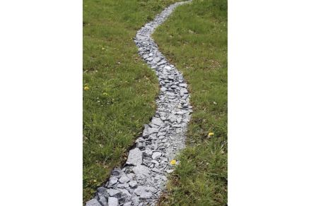 """Steinmetzmeister Erich Trummer nahm das Thema wörtlich und zerbrach den Kubus in viele kleine Einzelteile. Die verlegte er als """"Steinernen Faden"""" auf dem Gelände."""