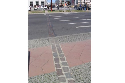 """A ribbon of cobblestone meanders through the center of Berlin where the Wall formerly separated the city. Photo: Shizhao / <a href=""""https://commons.wikimedia.org/""""target=""""_blank"""">Wikimedia Commons"""