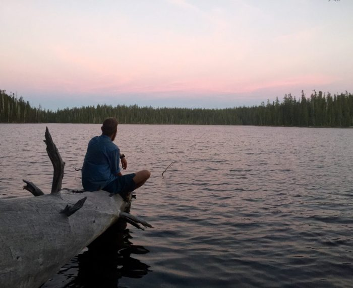 Mountain Man gazing out over Charlton lake at sunset from a dead log extending into the water
