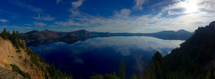 Blue sky reflected against the mirror surface of Crater Lake