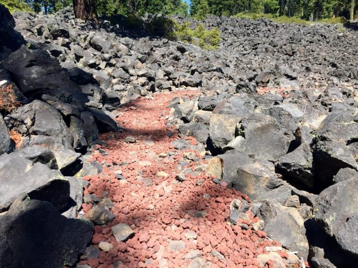 PCT following a path of crushed red stone through a field of black lava rocks