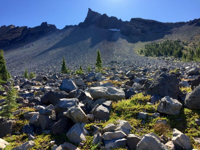 Sunlight over fields of rock leading up to the pointy summit of Mt. Thielsen