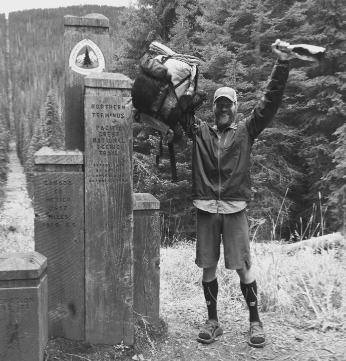 Mountain Man holding backpack and a bottle of champagne at the PCT northern terminus