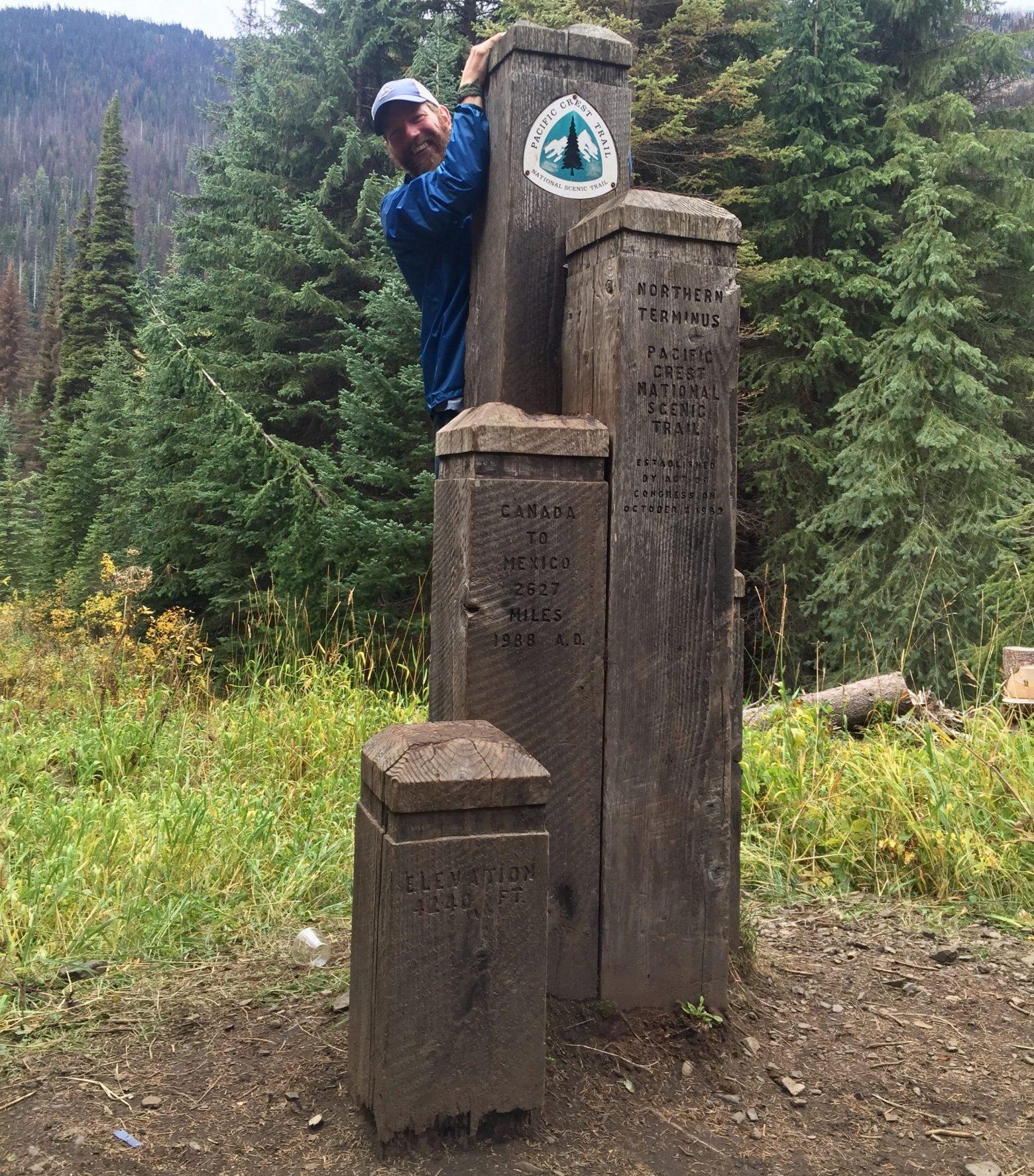 Mountain Man hiding behind wooden border posts at PCT northern terminus