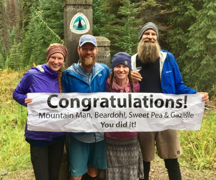 Mountain Man, Gazelle, Beardoh and Sweet Pea holding a congratulations banner at the PCT Northern Terminus
