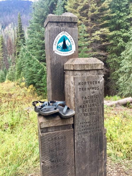 Final pair of hiking sandals resting on Canadian border posts at PCT northern terminus