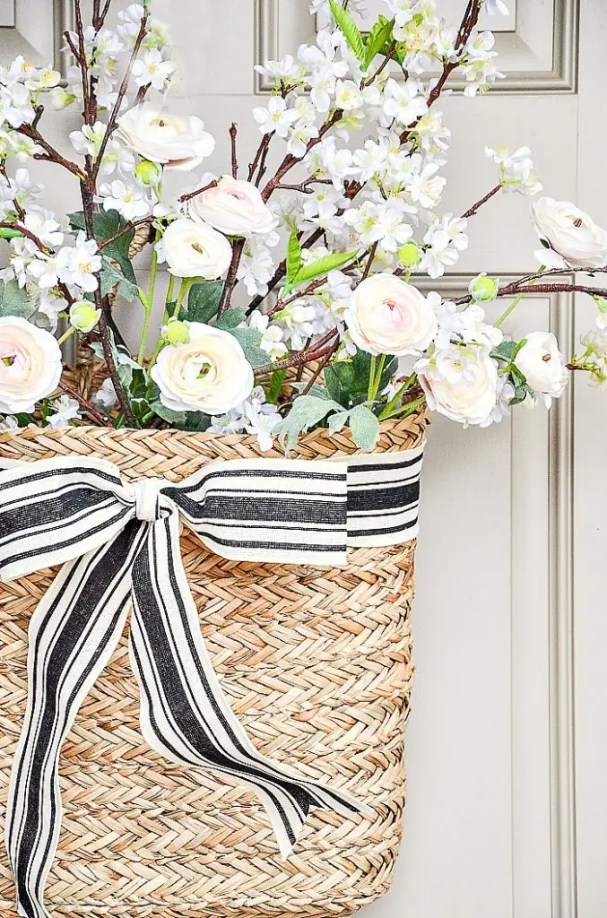 basket on the front door filled with apple blossom branches and ranunculus. Ties with a black and white ribbon
