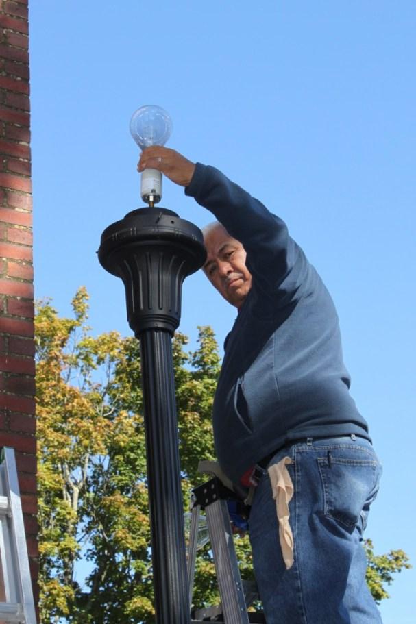 Antonio Aguilera changing lightbulb