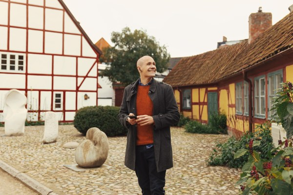 A man is standing by two half-timbered houses