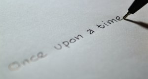 "A pen writes ""once upon a time"" across a white sheet of paper"
