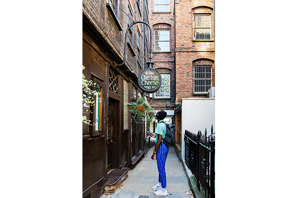 A young man in a green shirt is looking up at a sign that says Ye Olde Cheshire Cheese