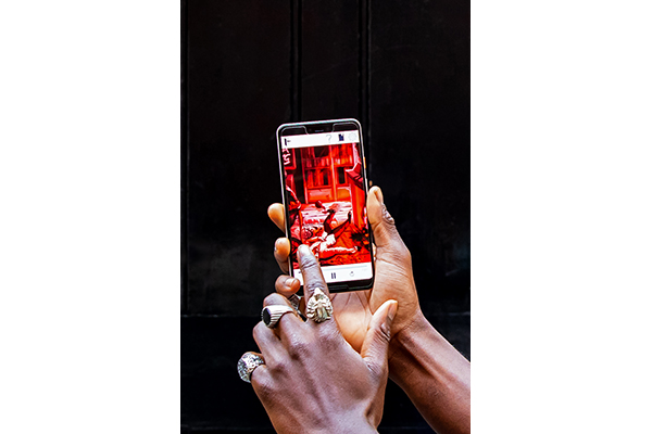 A close-up of a man's hands holding a smartphone. On the screen, an animated scene is visible