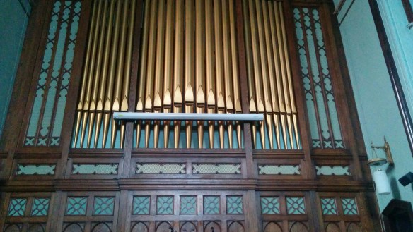 centered screen, below pipe mouths of organ