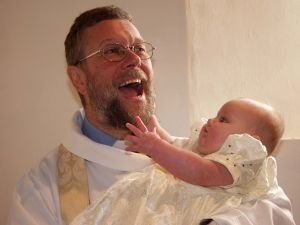Photo of Chris B (Vicar) holding a baby who is reaching for his beard