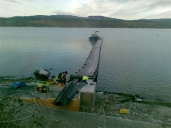 The pontoon is carefully positioned for attachment to the concrete anchor block