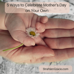cild's hand & mom's hand holding a daisy on Mother's Day