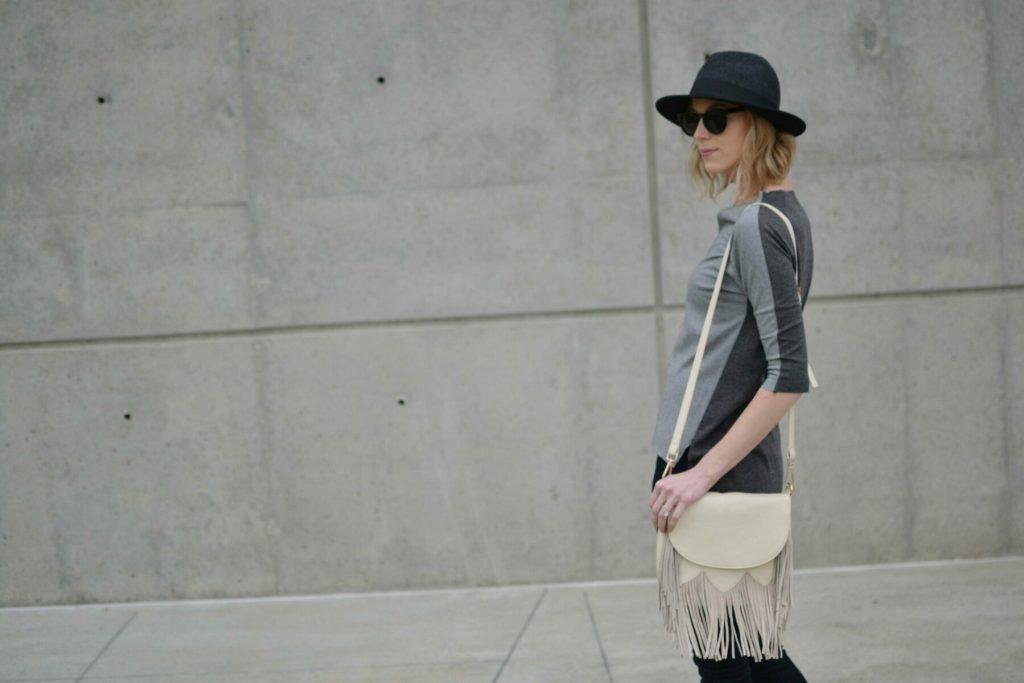grey top, black jeans, fringe bag, hat