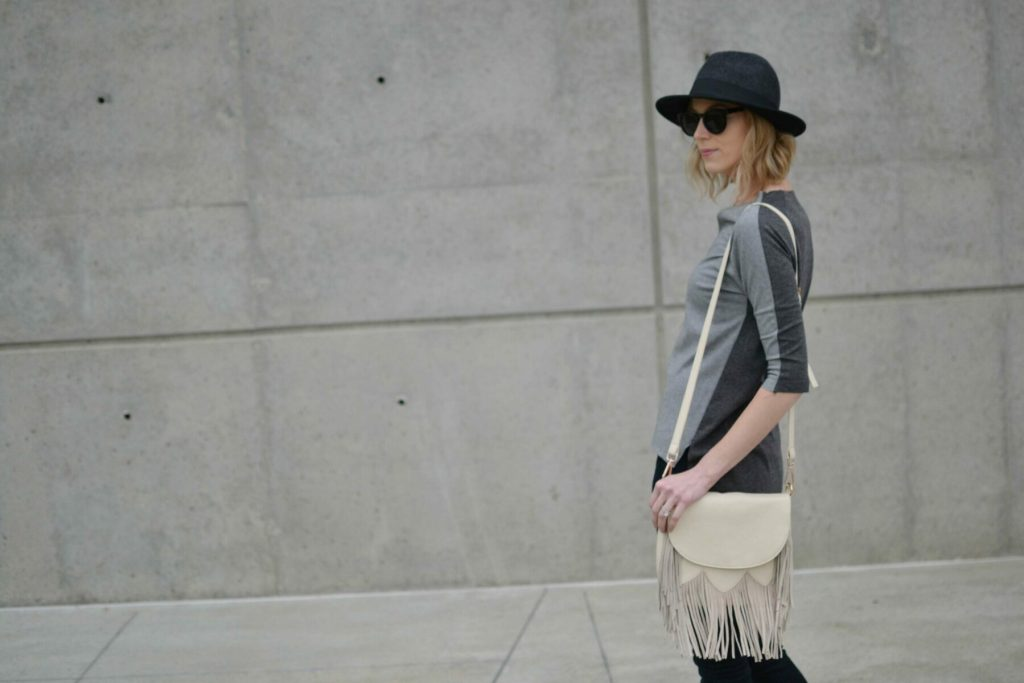 grey top, black jeans, fringe bag, hat