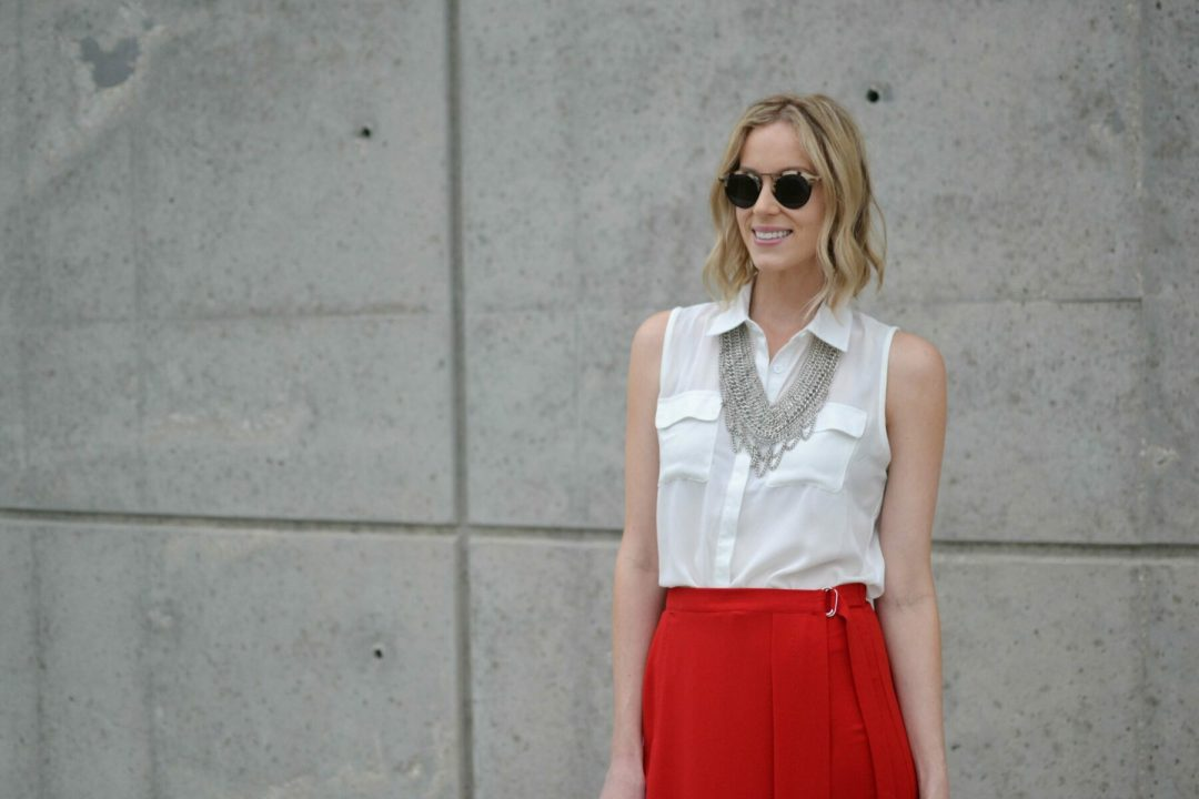 red culottes, white blouse, silver bib necklace, pink heels closeup