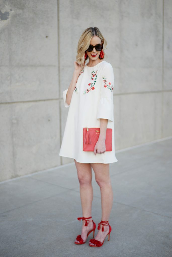 staying stylish on a budget, embroidered white dress, red tassel heels, red clutch