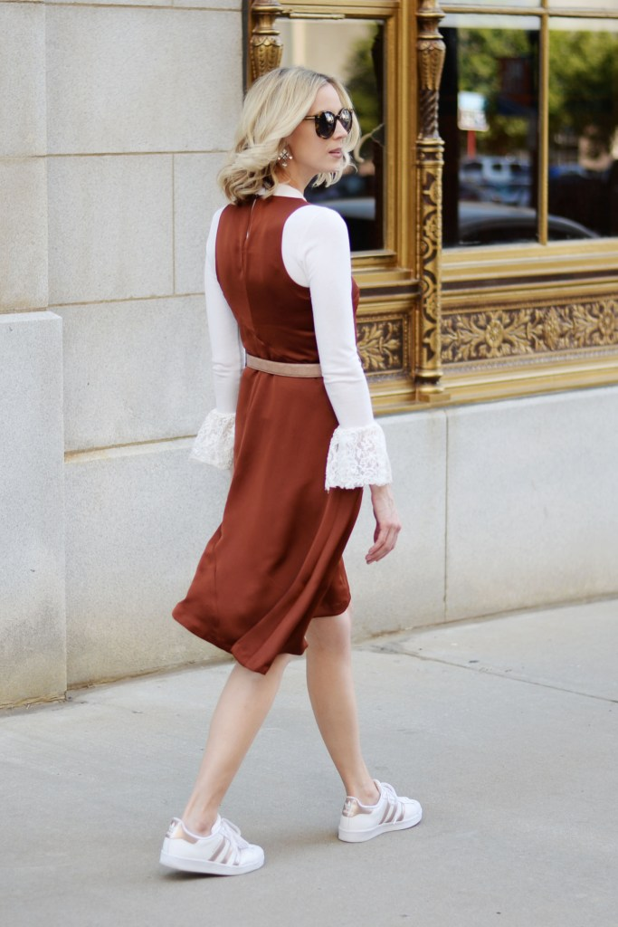 street style dress worn with sneakers over a bell sleeve top