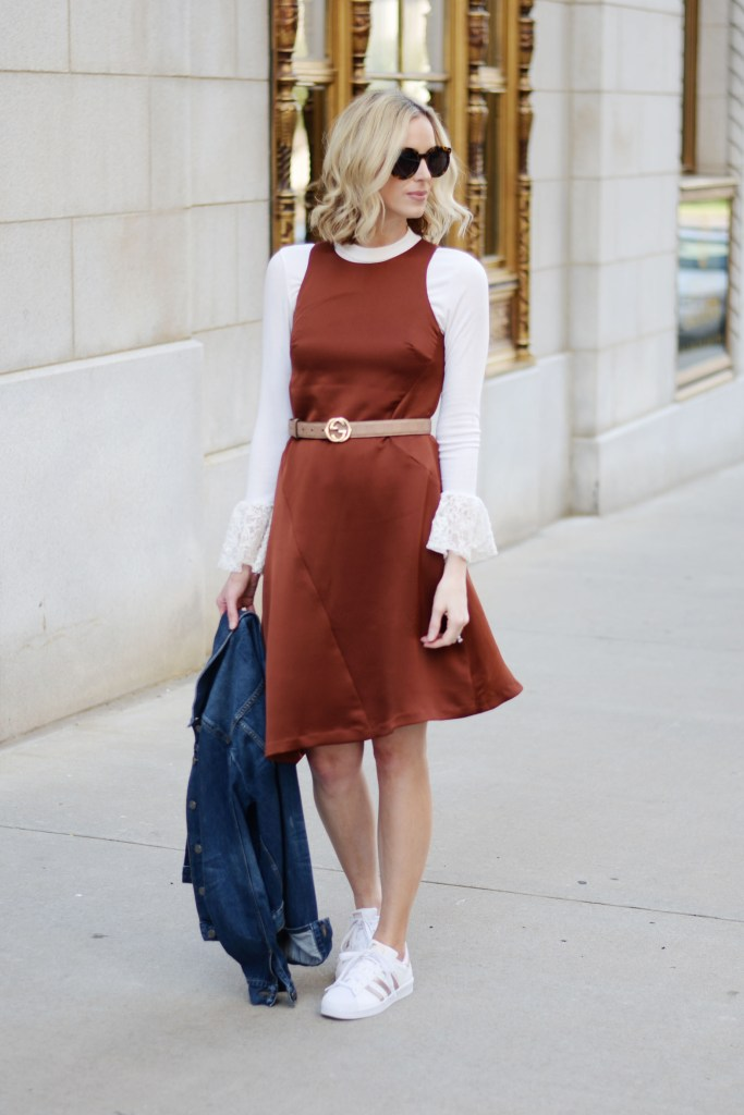 how to dress down a dressy dress, rust colored asymmetrical dress layered over a bell sleeve top with adidas superstars and jean jacket with gucci belt