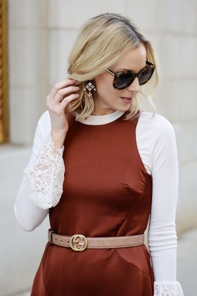 dressy statement crystal earrings with rust colored dress and belt