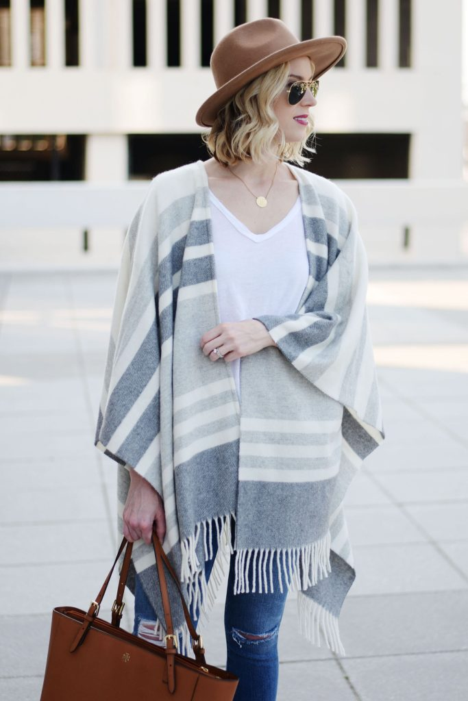 grey neutral poncho with white tee shirt and hat