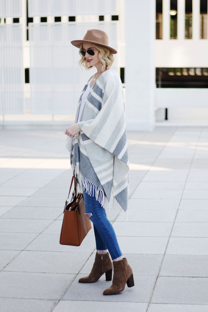 how to style a poncho with jeans, grey striped poncho with jeans and a hat