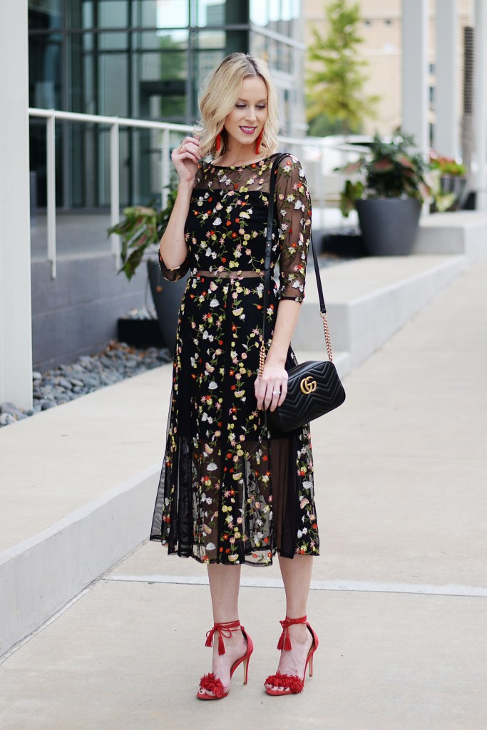black floral midi dress with red heels, sheer panel cut outs, red statement earrings
