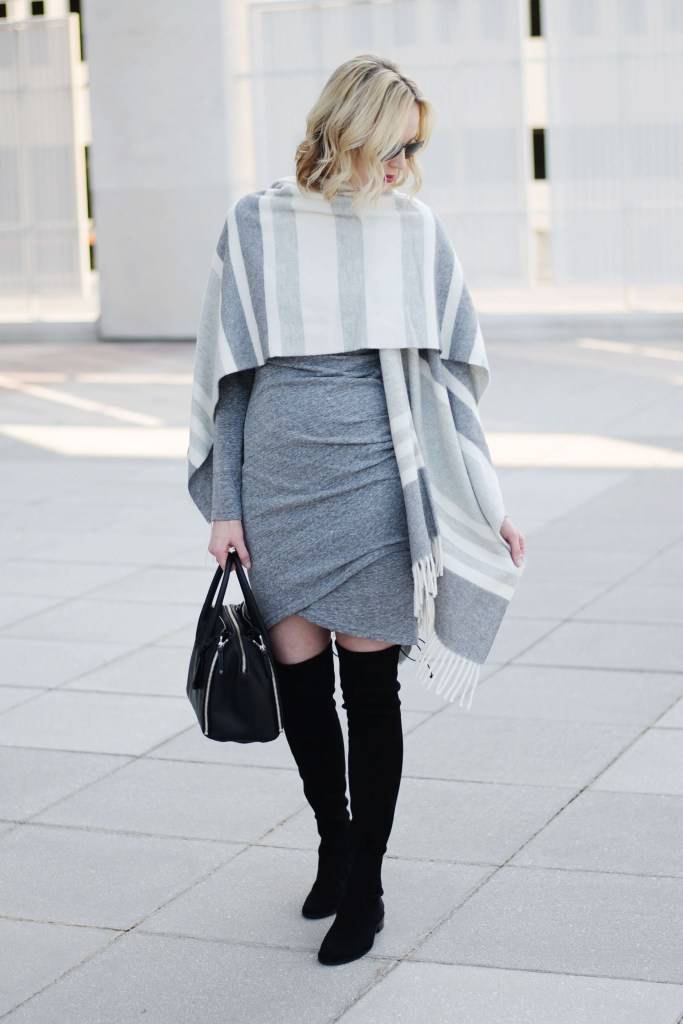 how to style a poncho with a dress, grey ruched dress with black over the knee boots and grey striped poncho draped over shoulders as wrap