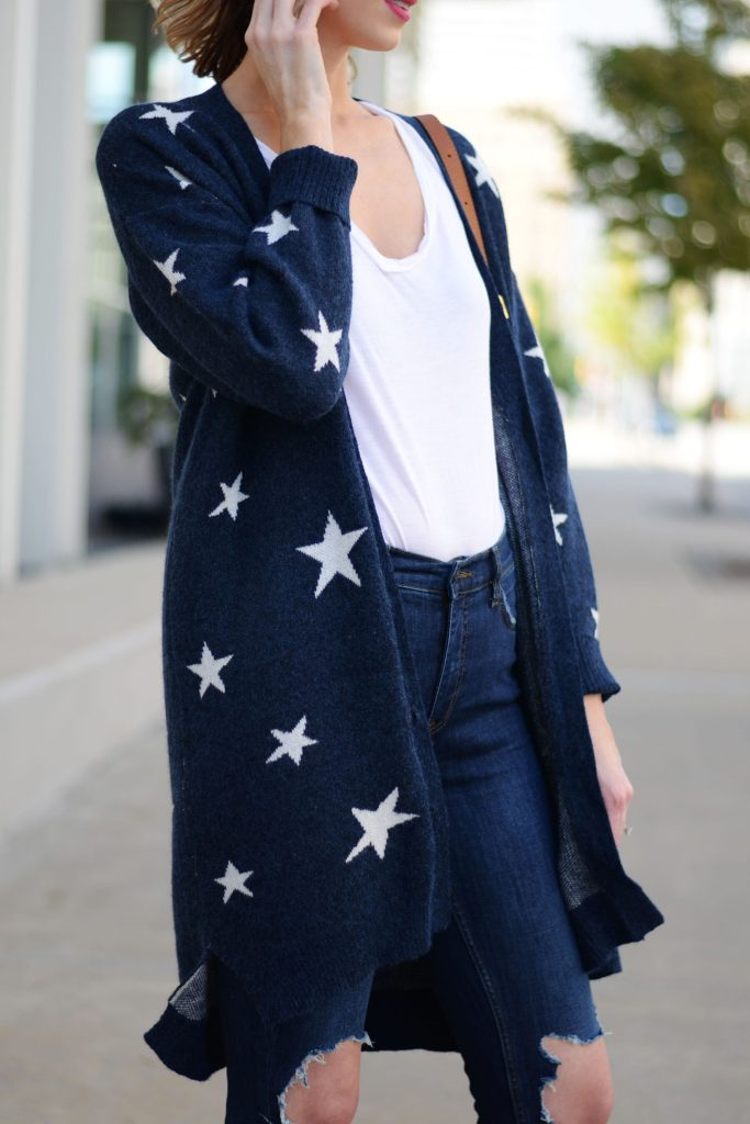 blue and white star cardigan with white t-shirt tucked into jeans