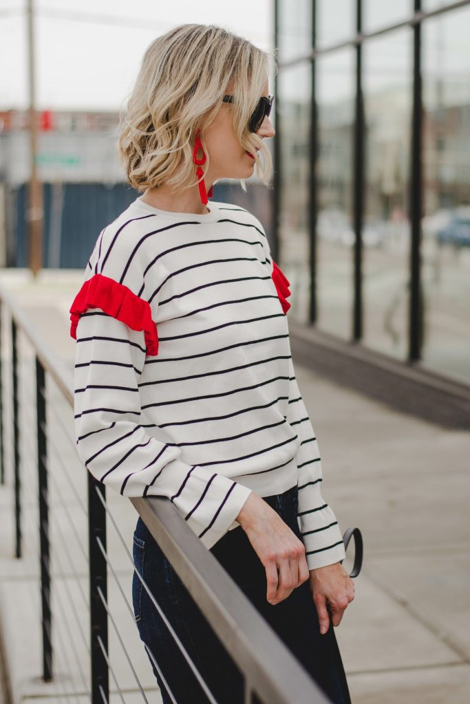 striped top with red ruffle shoulder detail and red statement earrings
