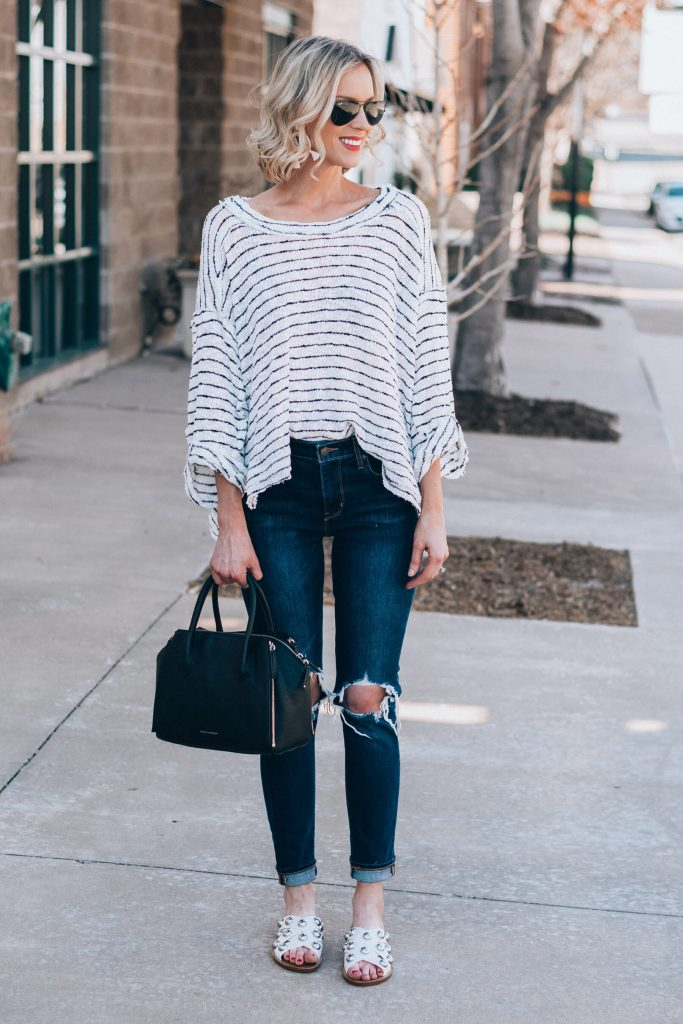 comfy oversized top with jeans and studded white slide sandals