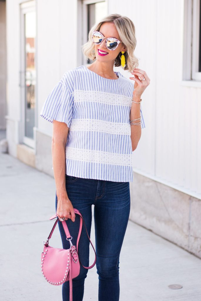 yellow statement earrings with blue and white outfit and pink bag