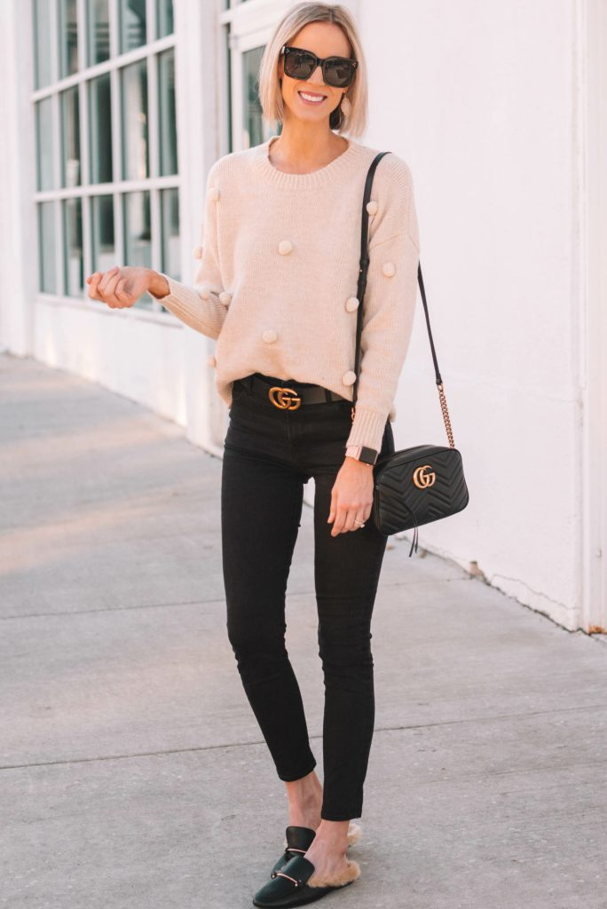 cute and fun cream pom pom sweater with black skinny jeans and gucci dupe slides