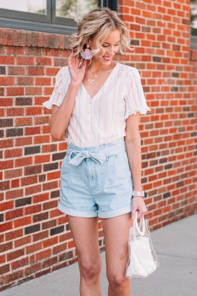 light wash denim paperbag waist shorts with a light colored shirt and fun earrings