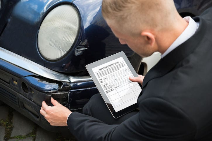 40751871 - insurance agent inspecting damaged car with insurance claim form on digital tablet