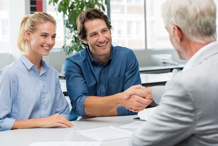 58367035 - handshake of a senior financial advisor with a young man and his girlfriend. businessman handshake with couple during meeting signing agreement. real estate agent shaking hands with happy smiling couple.
