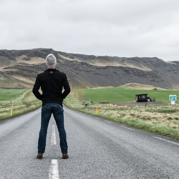 image of man standing in the middle of a road, seeing his future stretch out before him