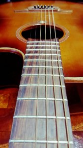 A Lag Steel string acoustic guitar focusing on the neck and strings. Stratford Music repairs and restrings guitars.