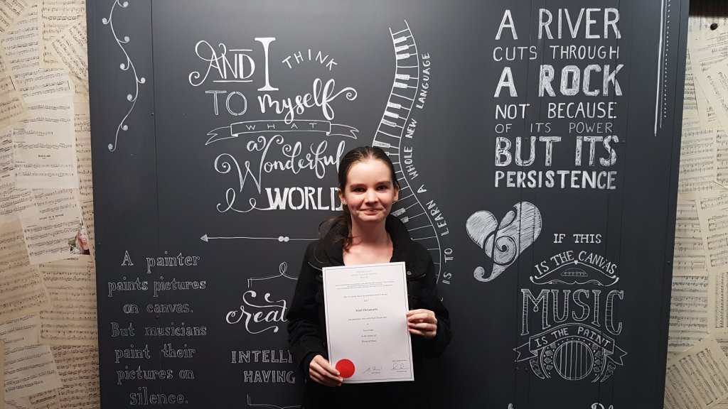 Niah holding her Grade 1 theory certificate after completing a music theory course at Stratford Music.