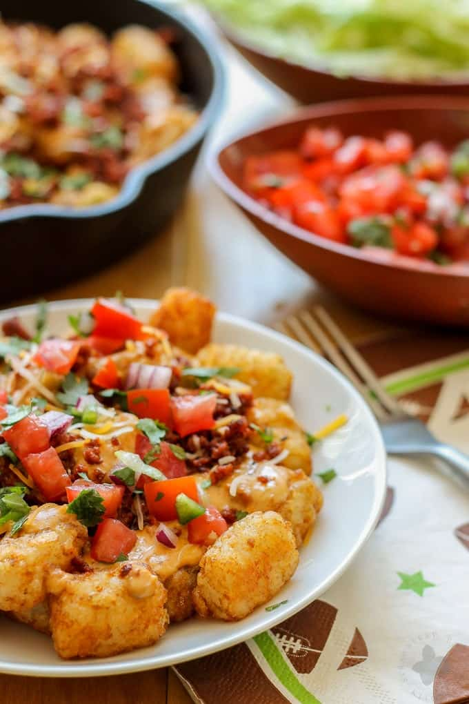 A classic twist on nachos, these Queso Fundido Totchos are a crowd pleaser. Serve them up for tailgating, an at home football party or serve them for dinner. Whatever you choose, they're sure to be a TOUCHDOWN and will have your guests going back for seconds! | Strawberry Blondie Kitchen