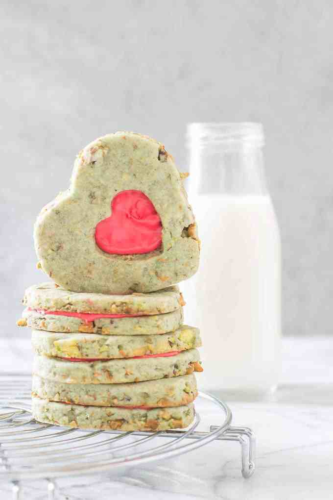 Your heart will grow three sizes with one bite of theseGrinch Sandwich Cookies. Pistachio shortbread cookies, with heart cutouts and red icing pay homage to one of childhood's favorite movies. | Strawberry Blondie Kitchen