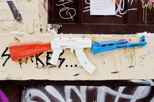 street art with a toy ak-47 in red, white and blue in NYC