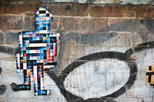 a colorful stikman street art piece made up of tiles in NYC