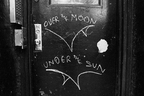 over the moon and under the sun graffiti on a door in the meat packing district of nyc